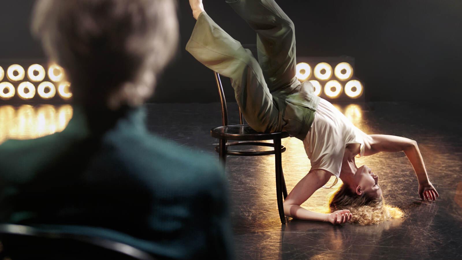 En dansare lutar sig mot en stol upp-och-ner vänt med huvud mot golvet, i rampljus under en åskådare tittar på.