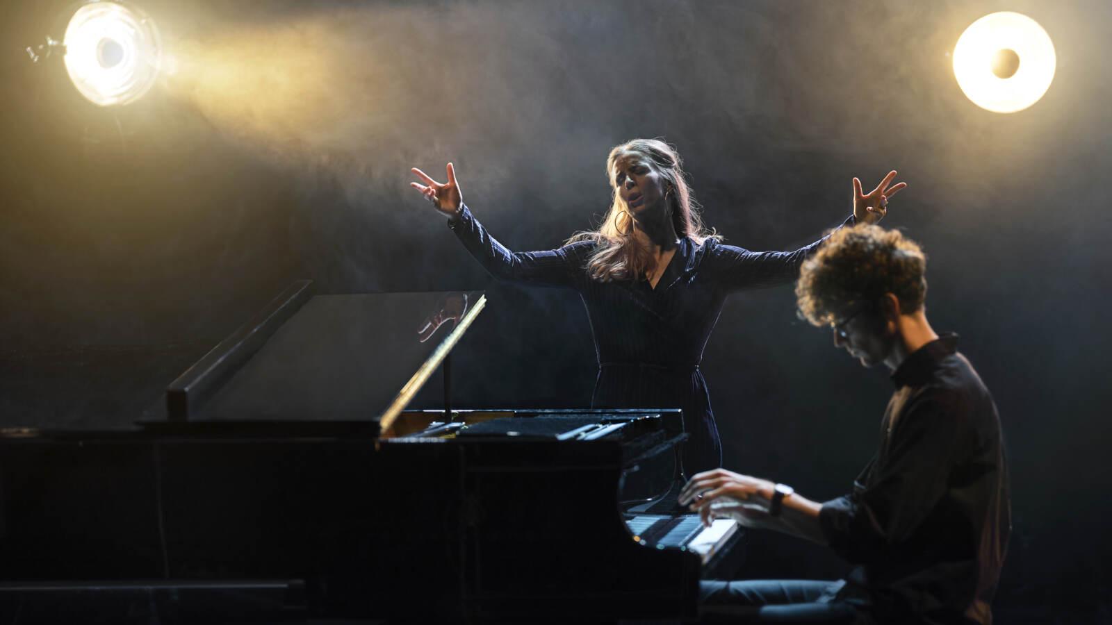 En sångare står mellan två spotlights i scenrök och en pianist sitter och spelar vid en flygel framför henne.