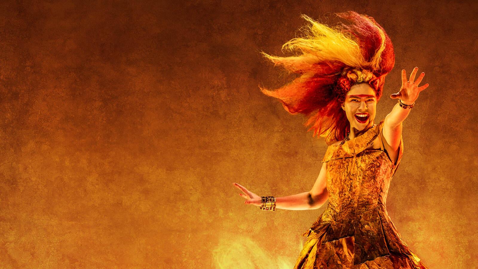 En sångsolist står i en rödorange eld-liknande scenografi, sträcker handen ut mot betraktaren och sjunger