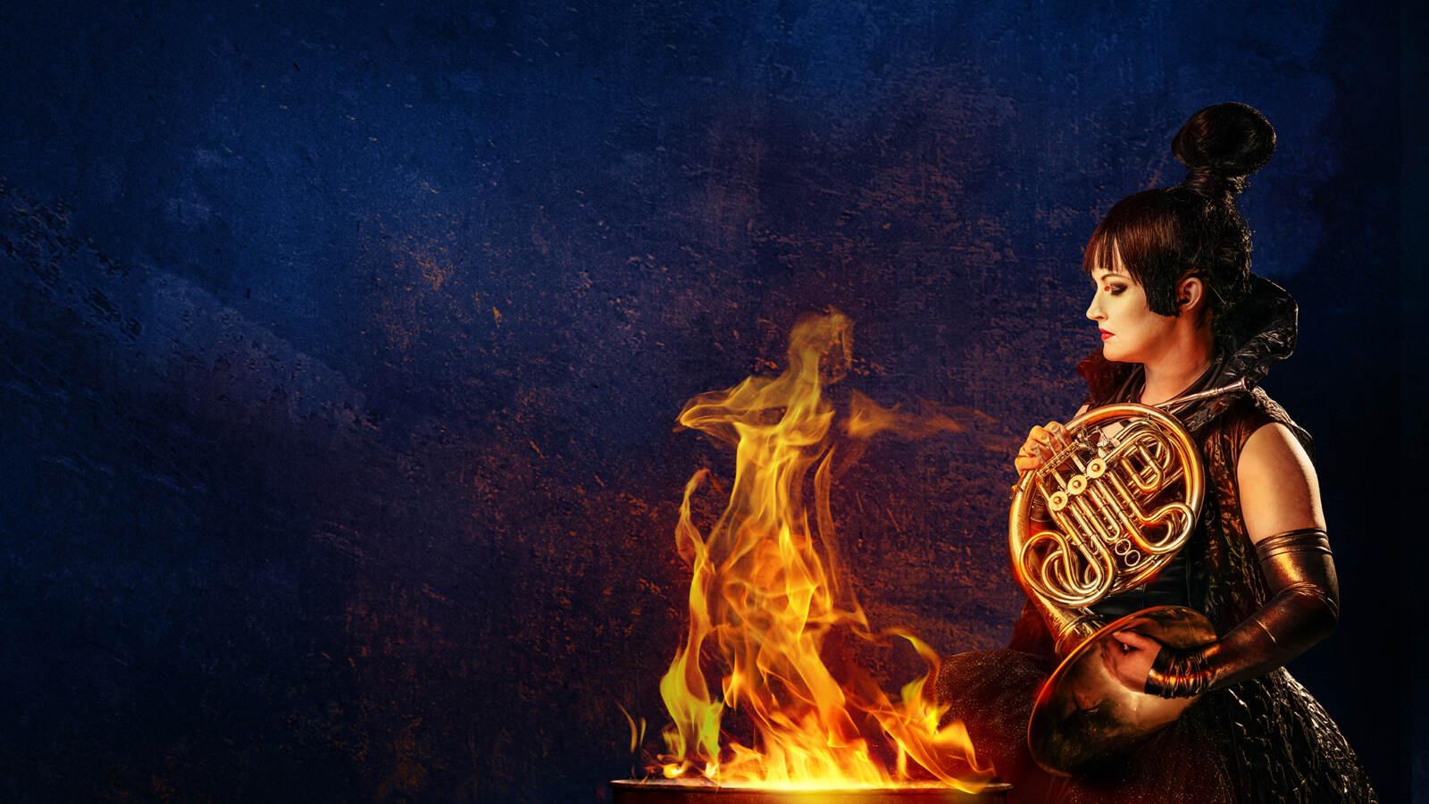 En hornspelare står och håller sin instrument framför en eld och tittar in i lågorna.