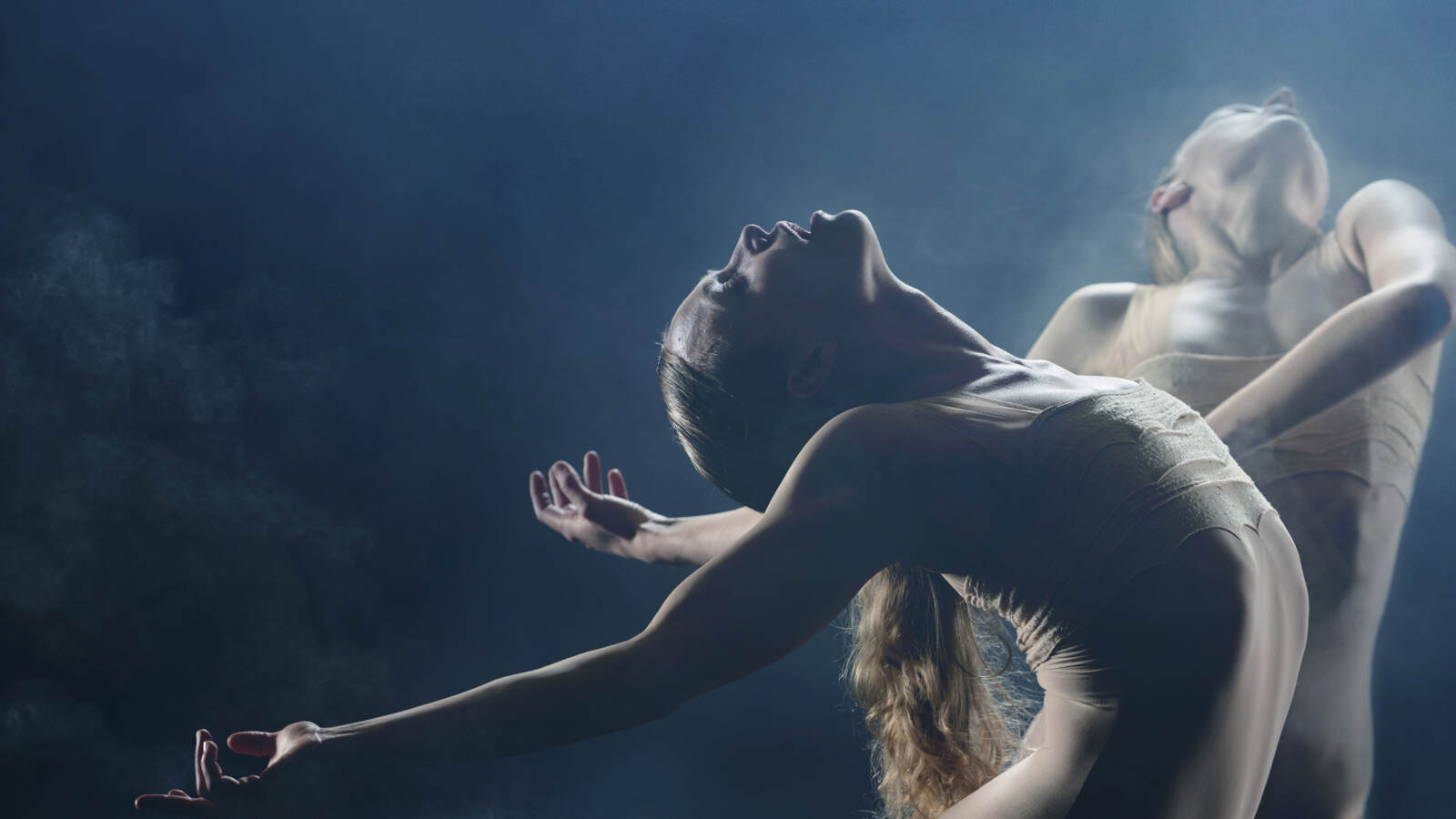 Two dancers stand under white stage lighting in smoke, the dancer in the foreground stands with arms outstretched behind her.