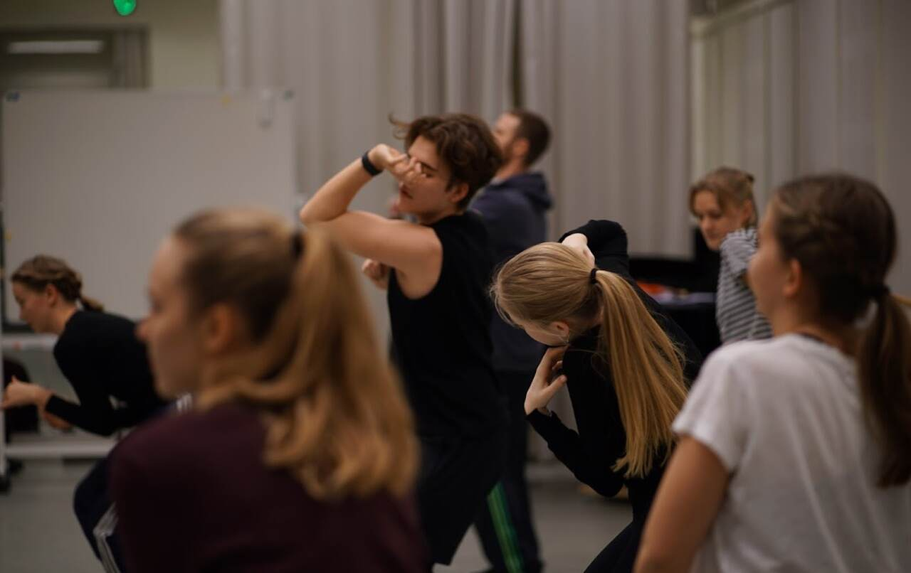 Several students dance expressively in a rehearsal room.