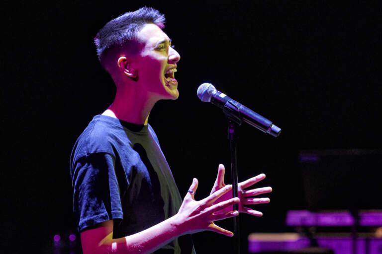 En ung sångare står i strålkastarljuset och sjunger.