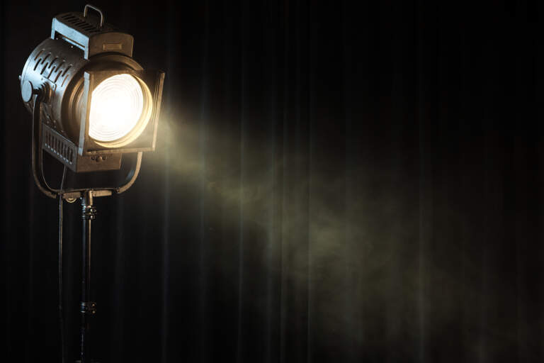 A lit spotlight showing theatrical smoke in the air against a background of dark curtains