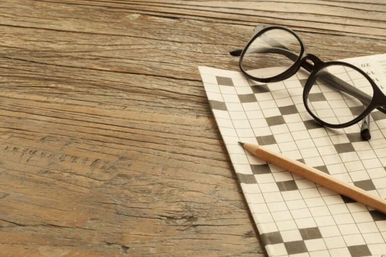 En blyertspenna och glasögon ligger på en vikt tidning som visar ett korsord. Tidningen liggger på ett träbord.