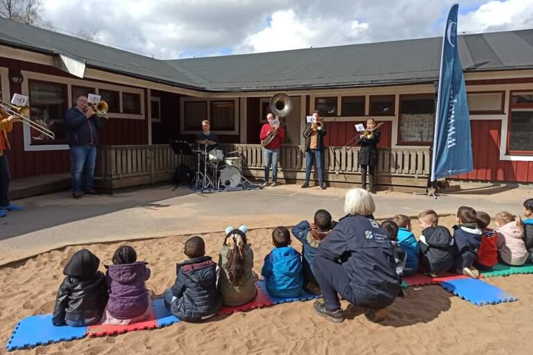 Några brassmusiker spelar i en skolgård för en grupp skolbarn som sitter och tittar med deras lärare.